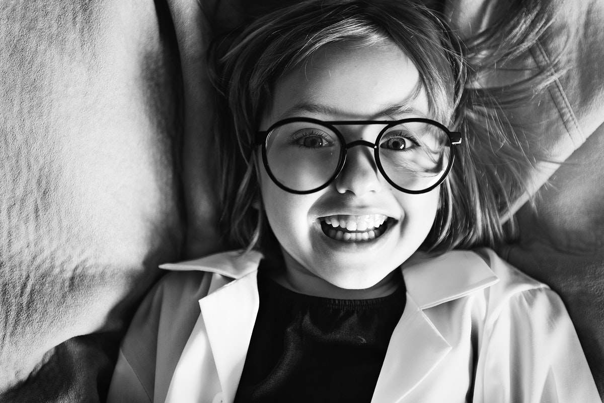 Smart little girl smiling and laying in bed