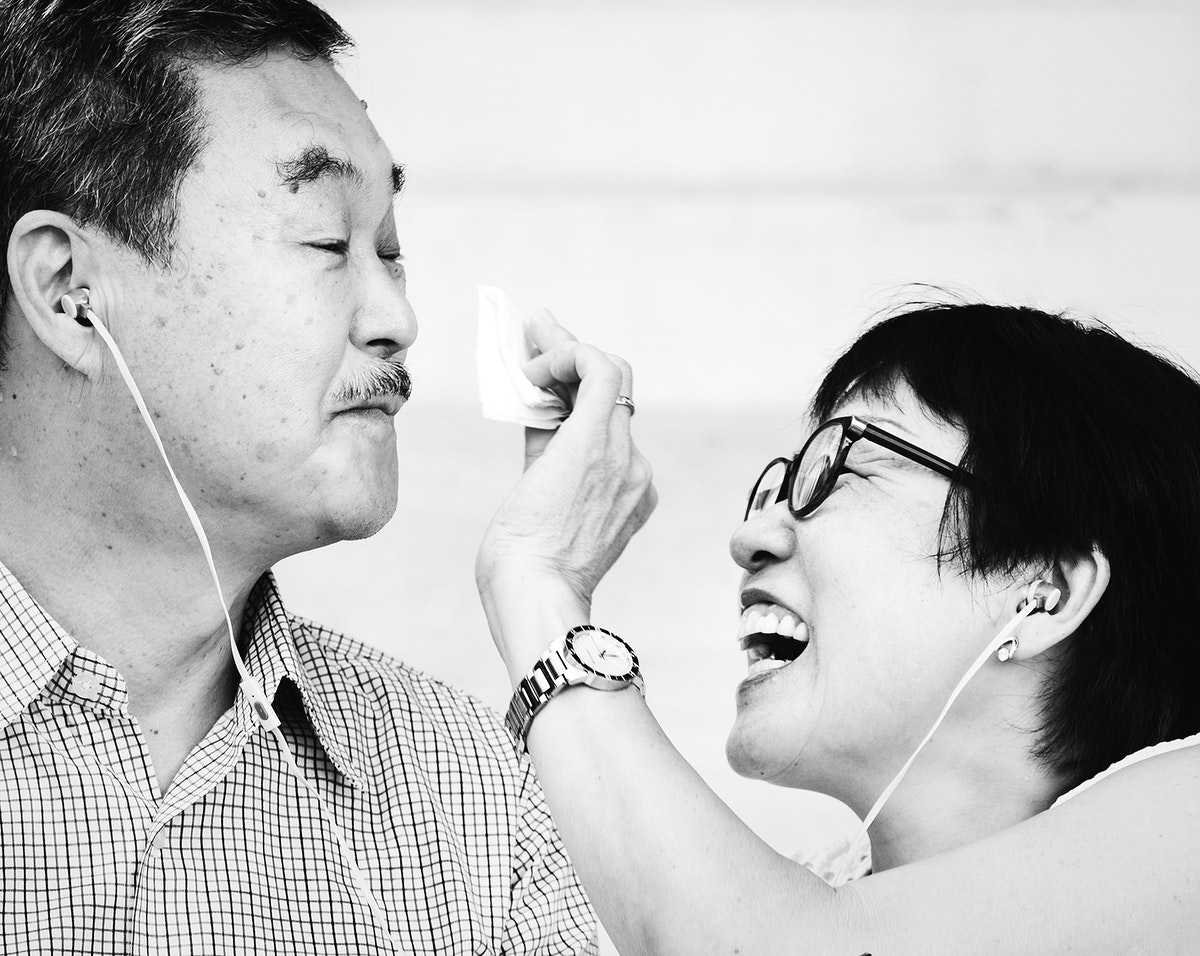 Senior Asian couple listening to music together