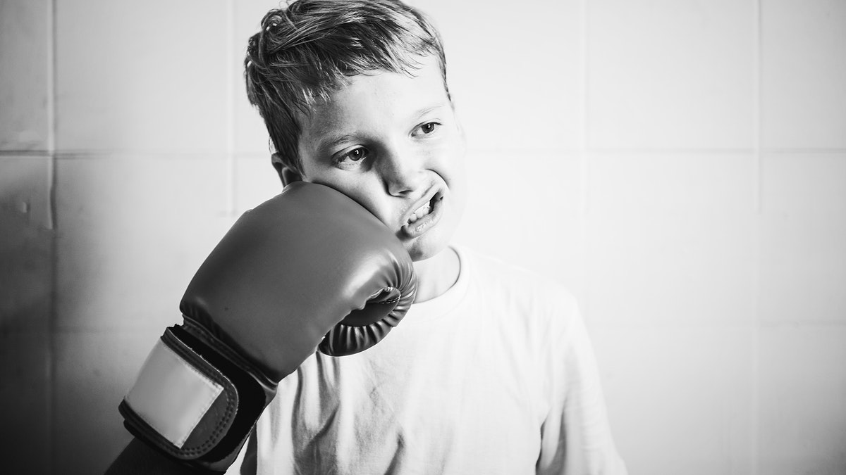 Little boy being playful with a boxing glove