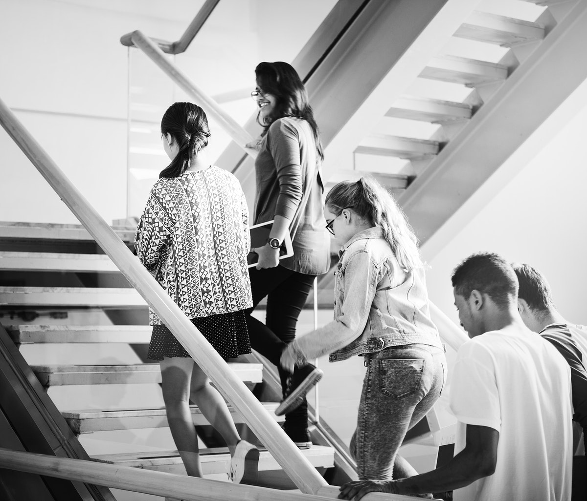 Group of teen students walking up the staircase