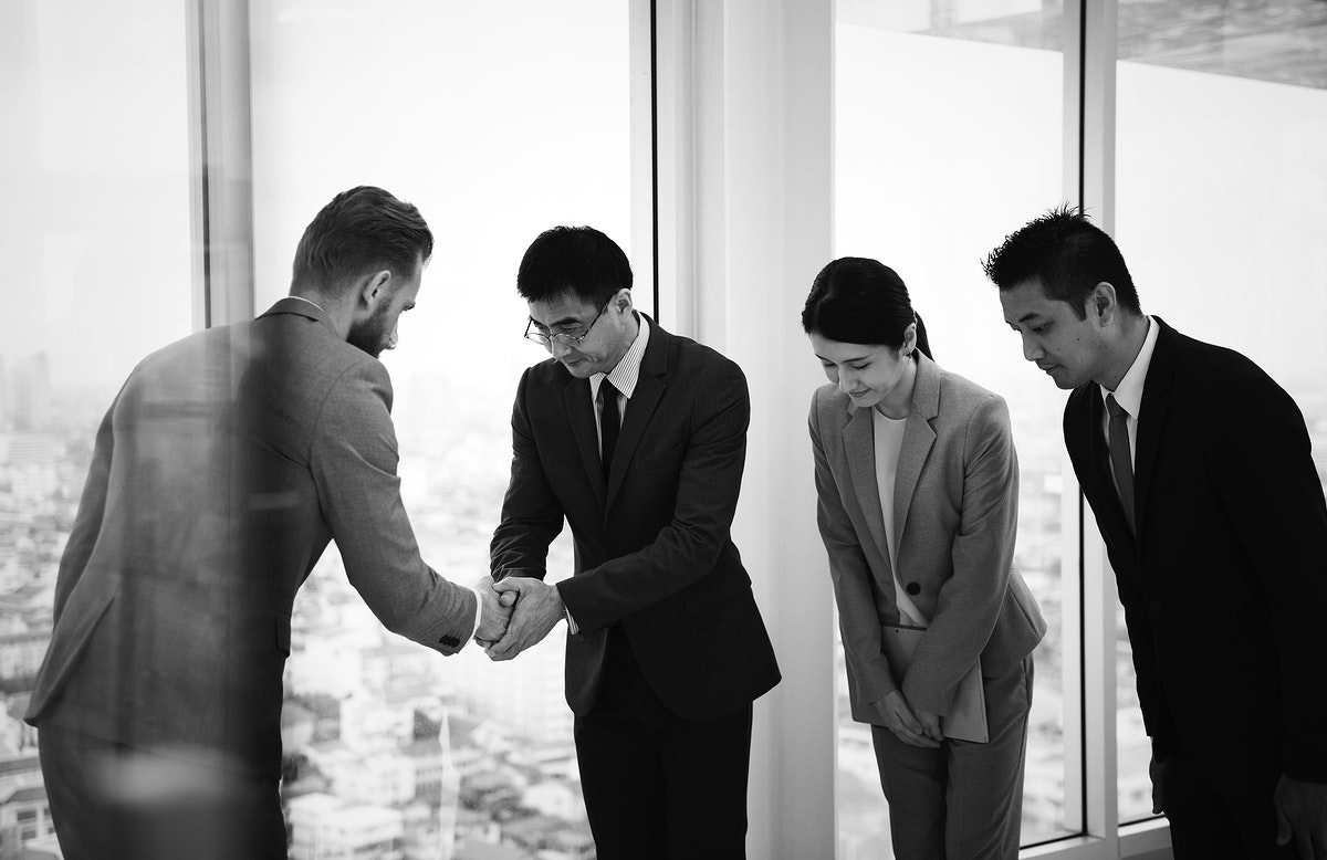 Japanese business people having a handshake with a colleague
