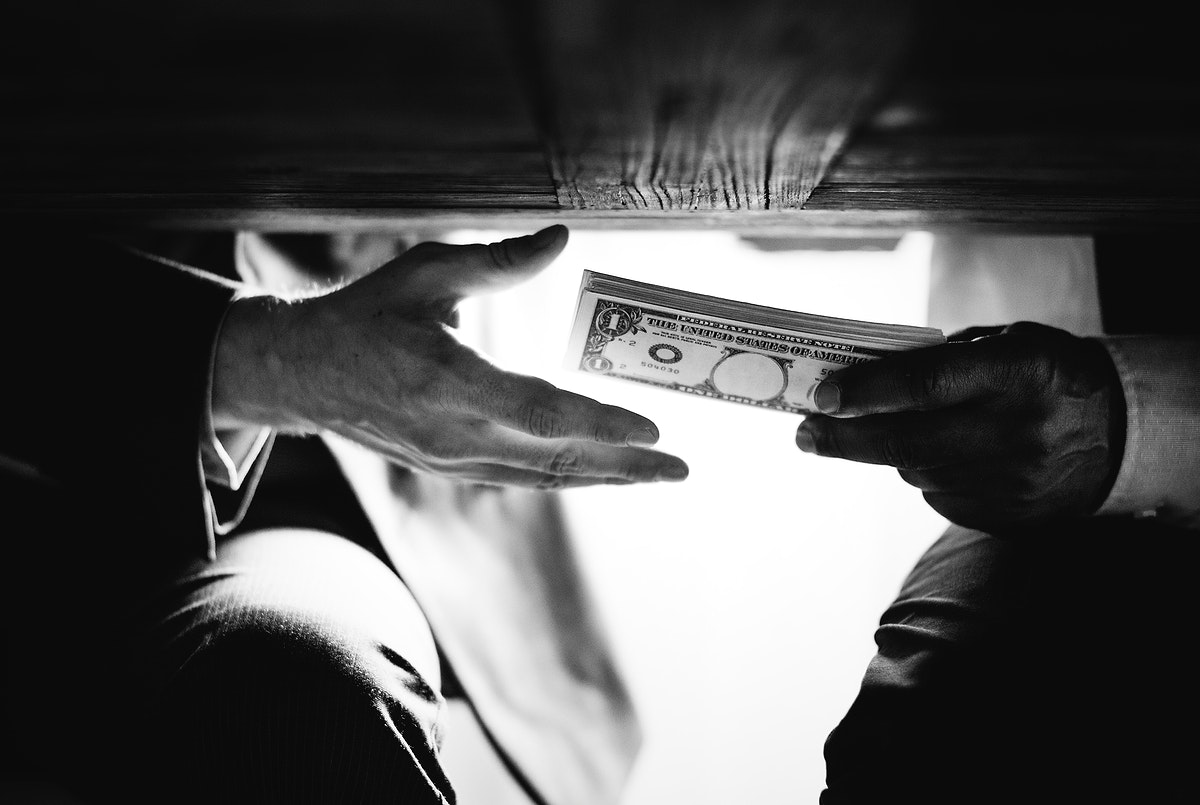 Hands passing money under the table corruption and bribery
