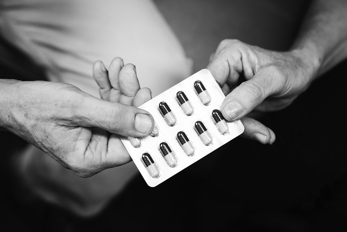 Hands holding medication capsules
