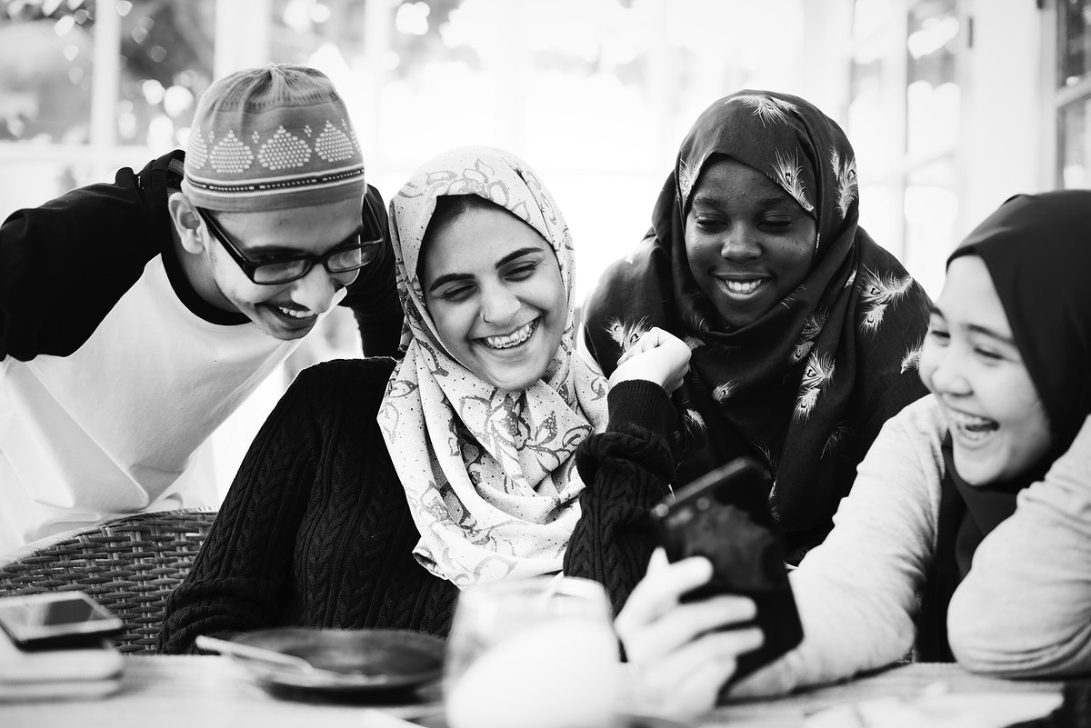 Group of Muslim students using mobile phones