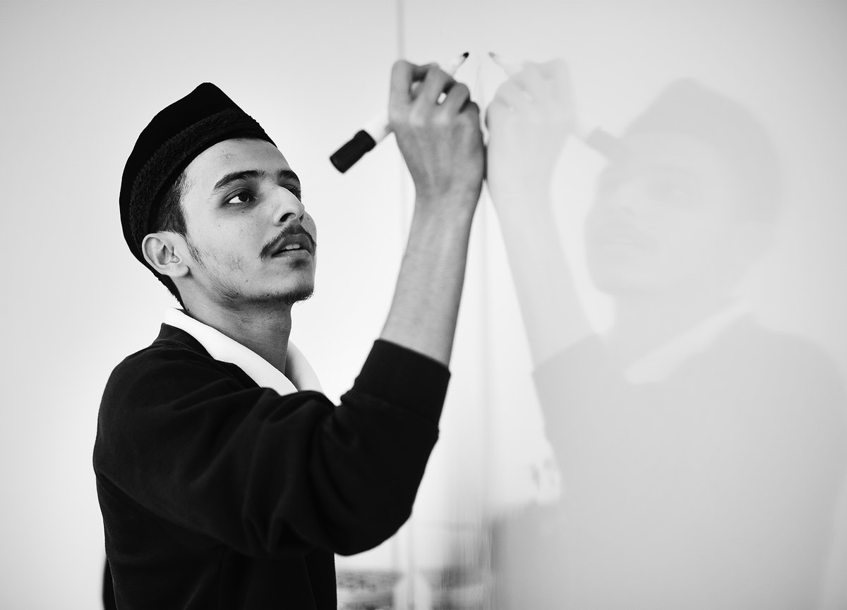 Young muslim man is writing on a white board