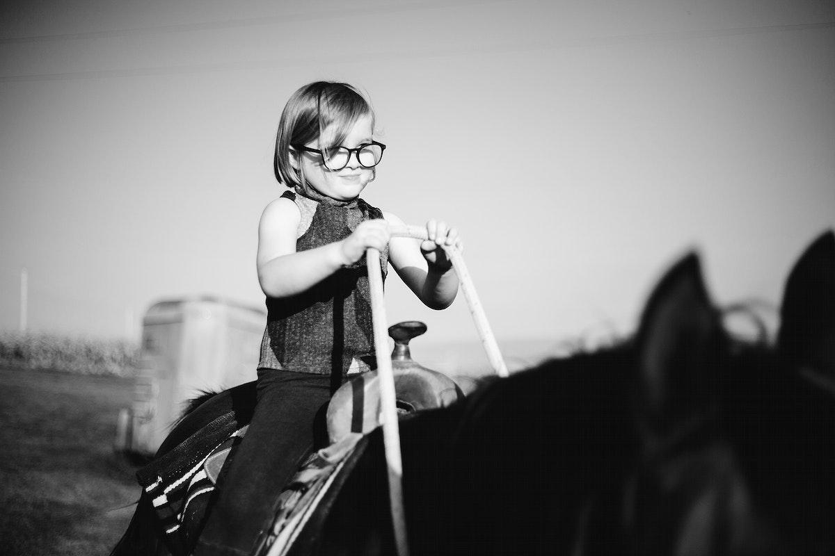 Young girl is enjoying horse riding