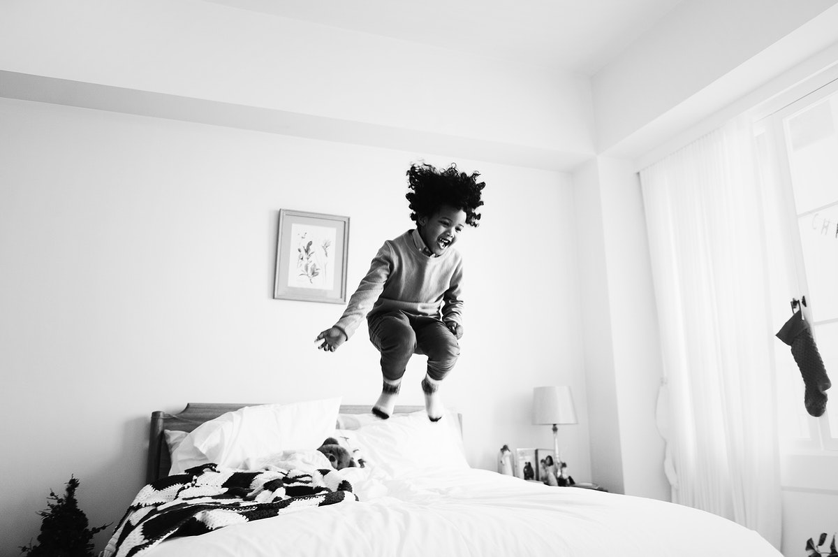 African kid having a fun time jumping on the bed