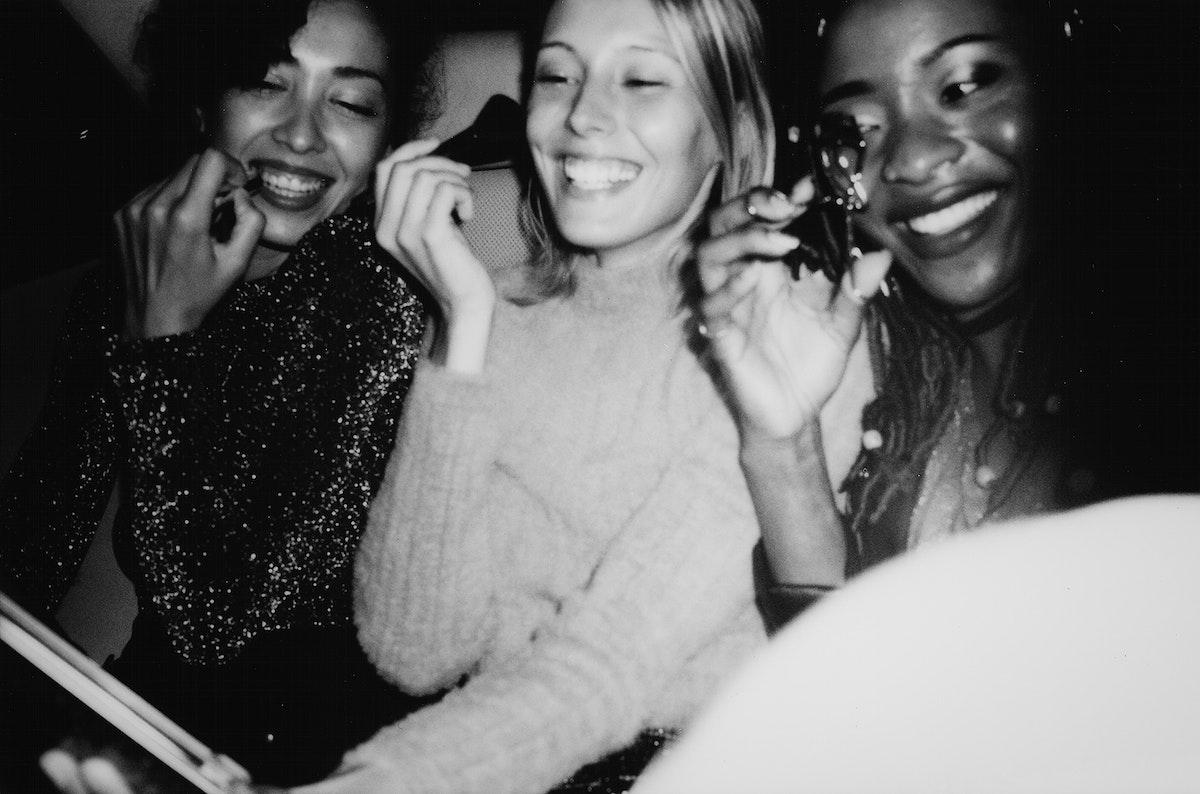 Diverse women applying makeup in a backseat
