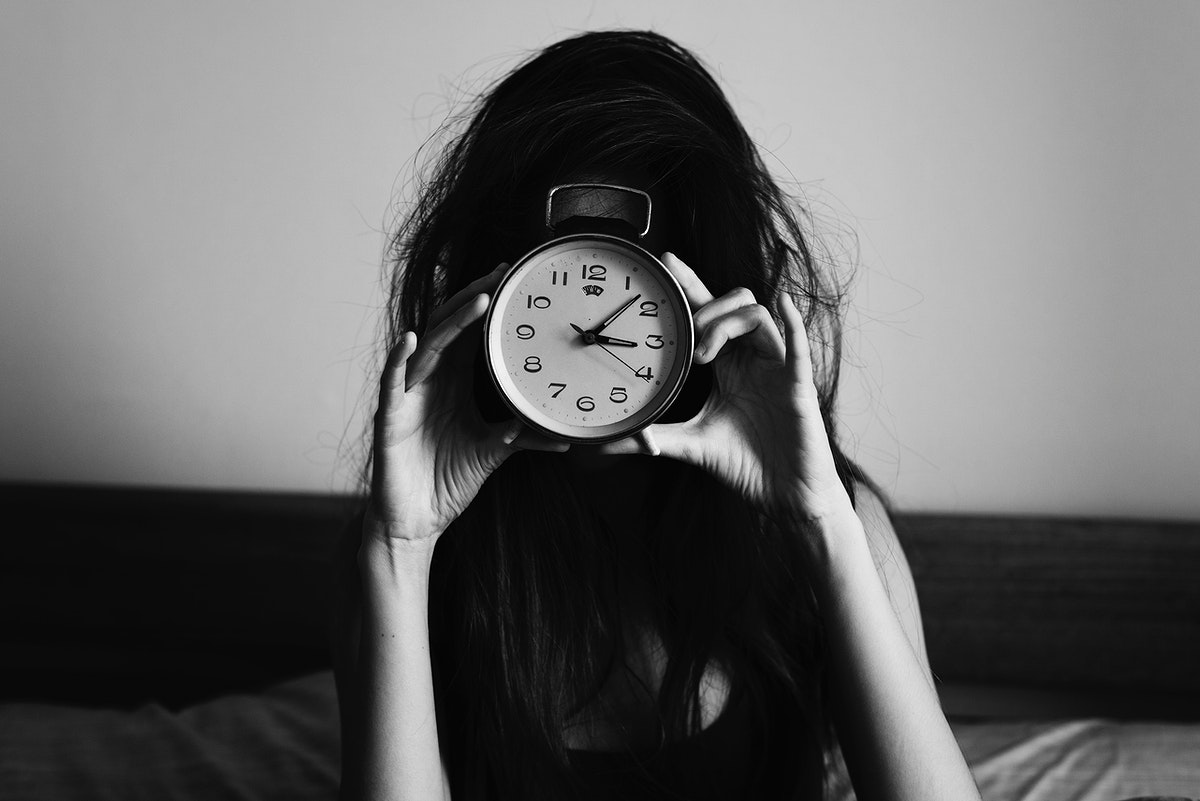 Girl holding a clock in front of her face