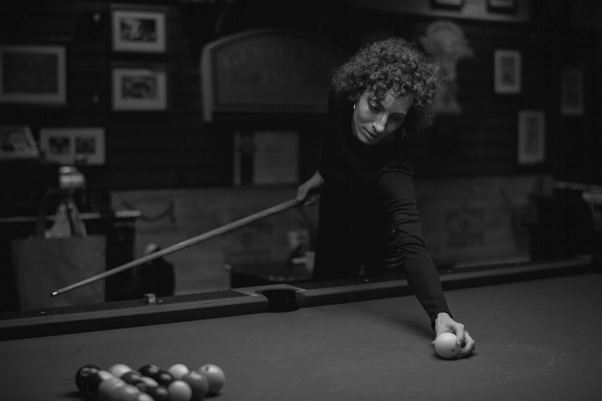Single woman playing pool at a bar