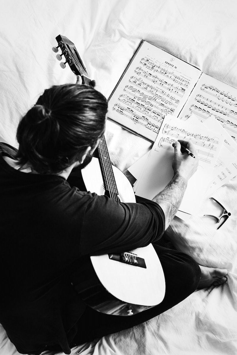 Man composing a song on a guitar