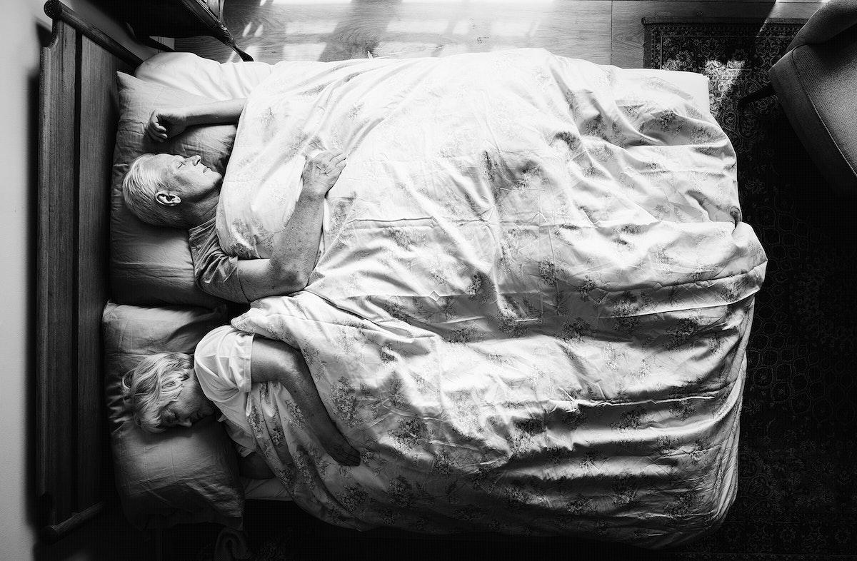 Elderly Caucasian couple sleeping in a bed