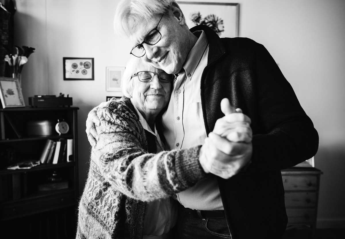 Senior couple dancing together at home