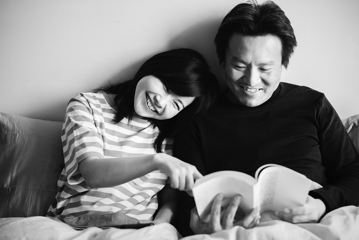 Asian couple reading a book in bed together