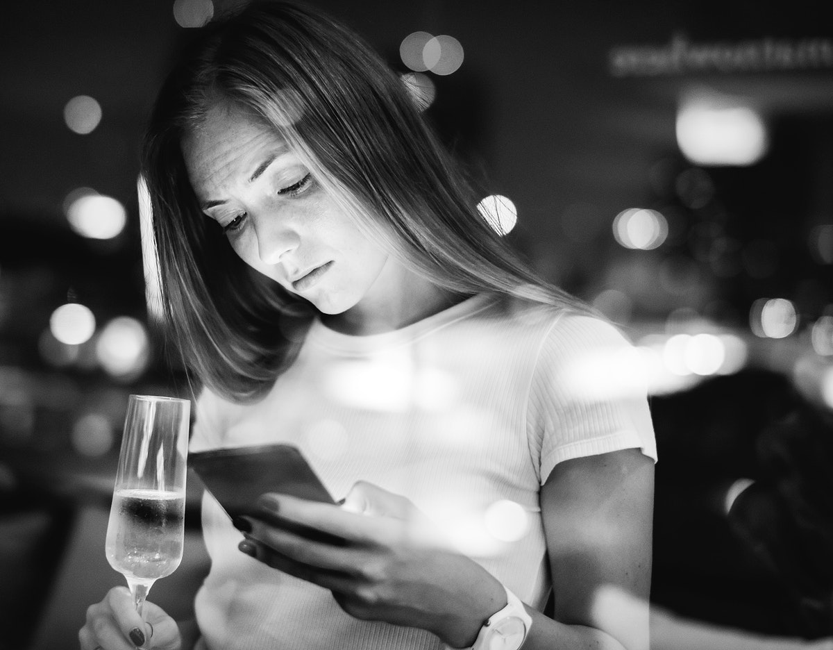 Woman using a smartphone at a rooftop bar