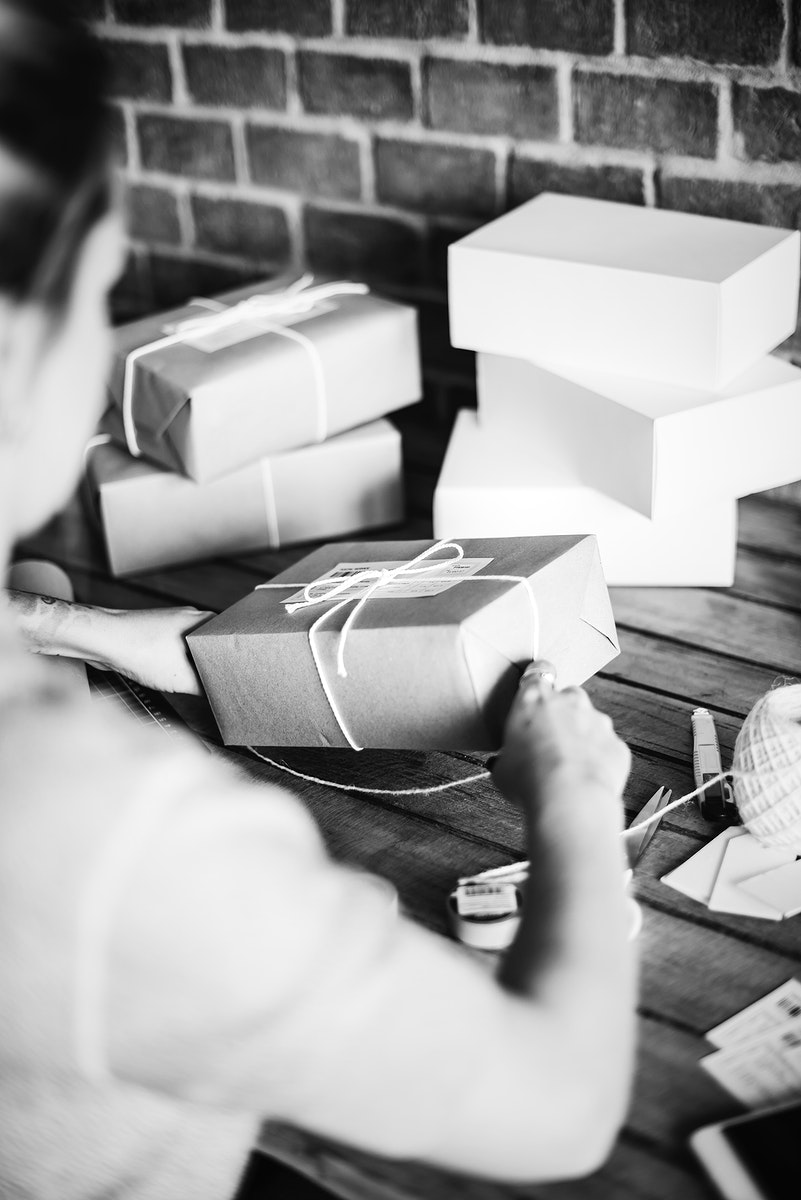 Woman wrapping a package by herself