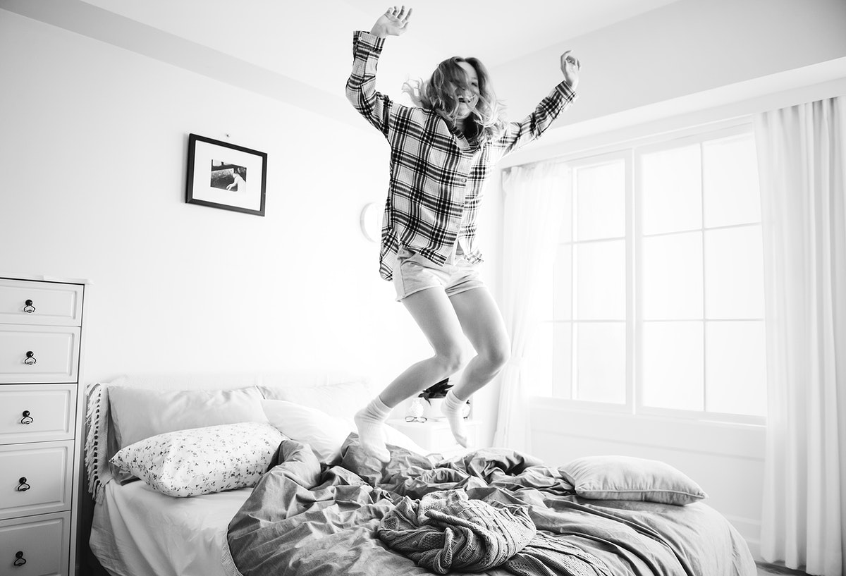 Caucasian girl jumping on the bed