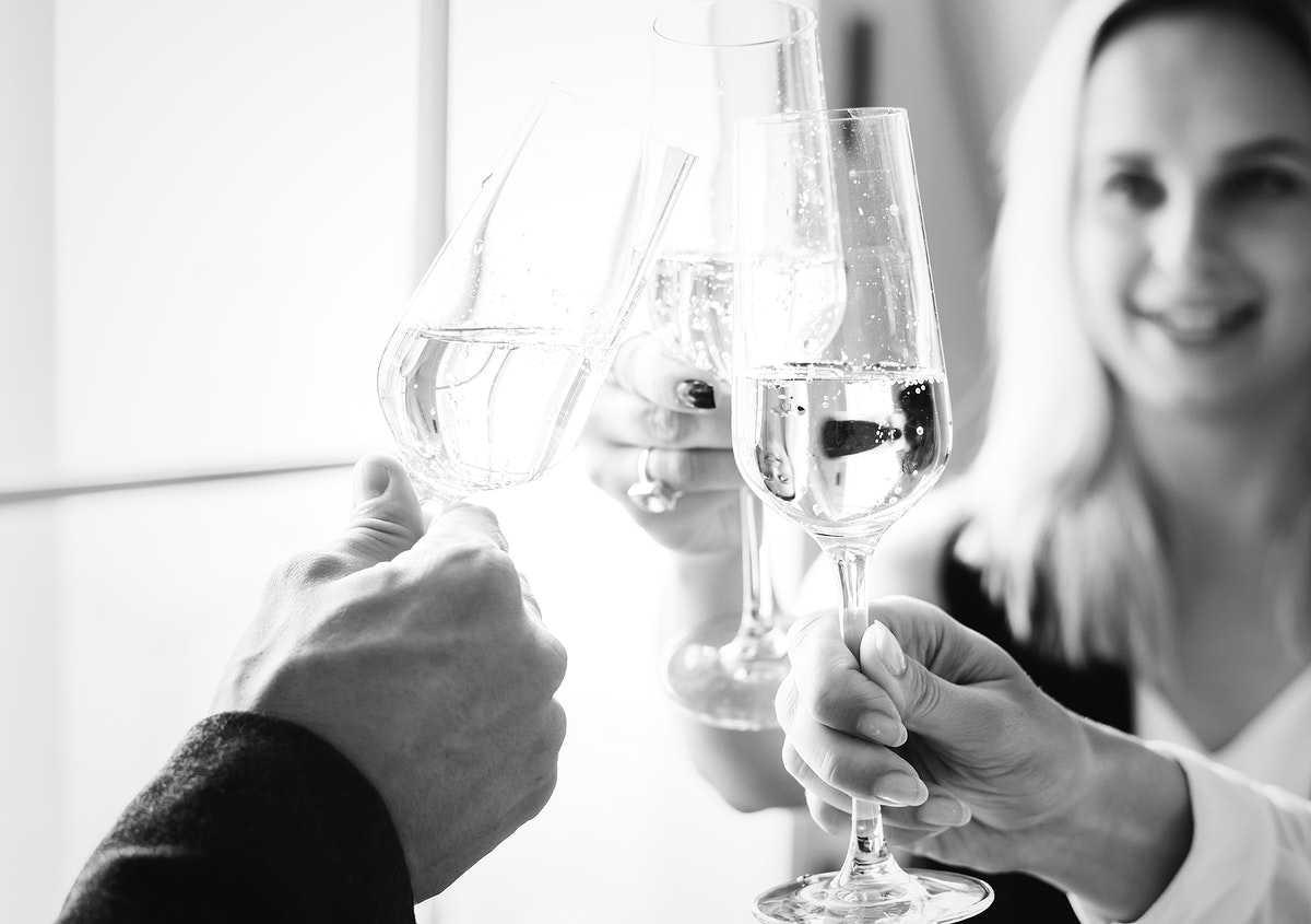 Closeup of people clinking wine glasses