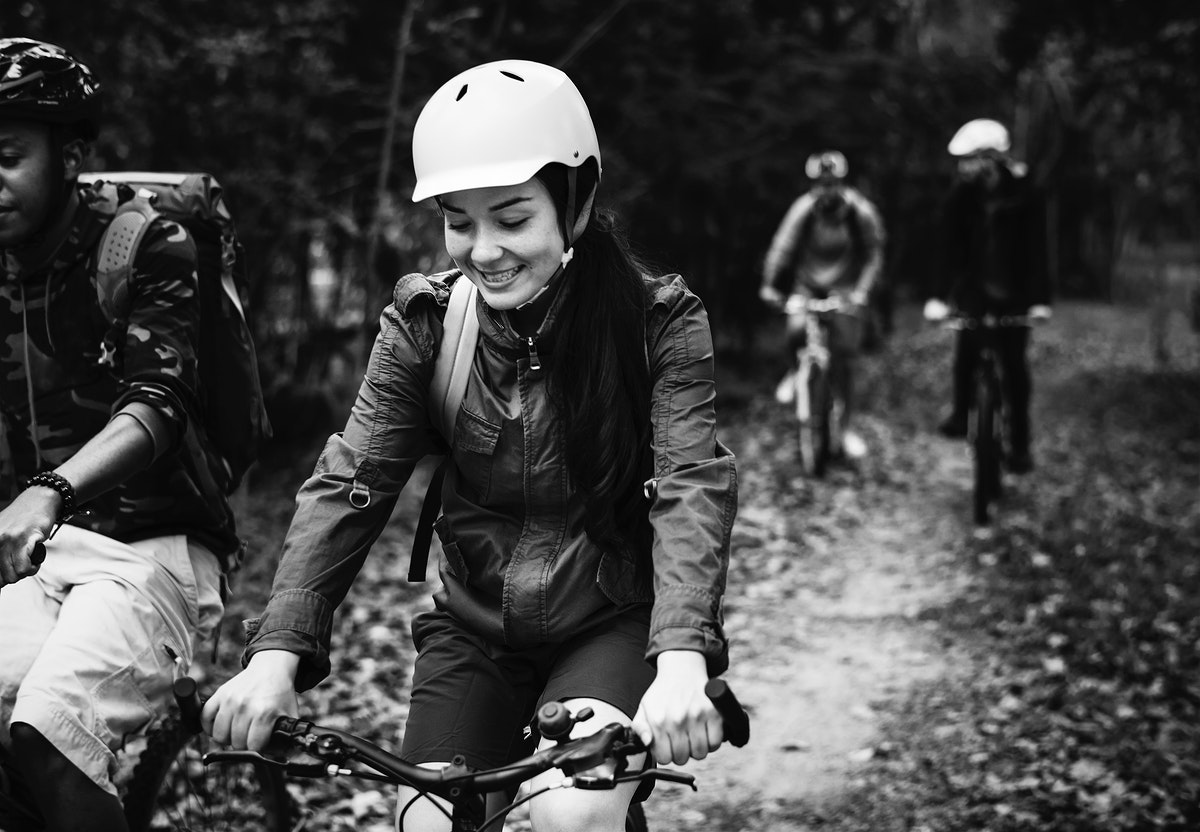 Friends riding a bicycle in the forest