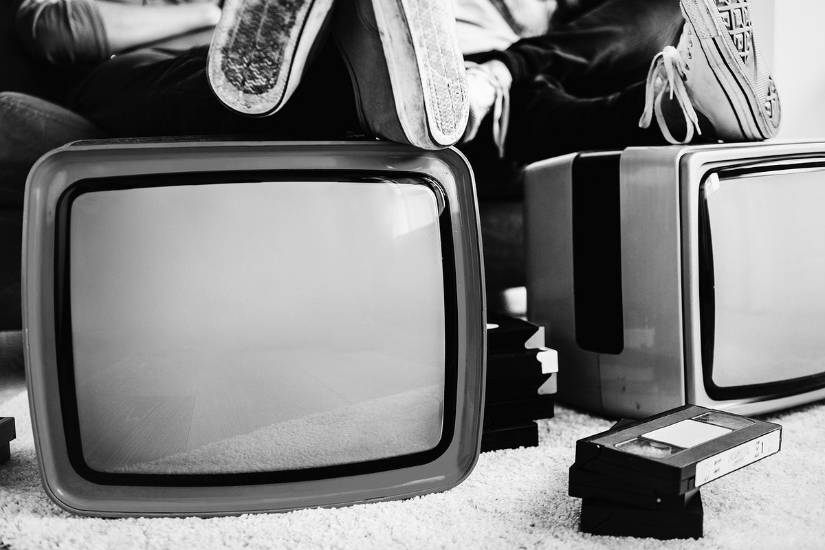 Two men putting legs on retro televisions