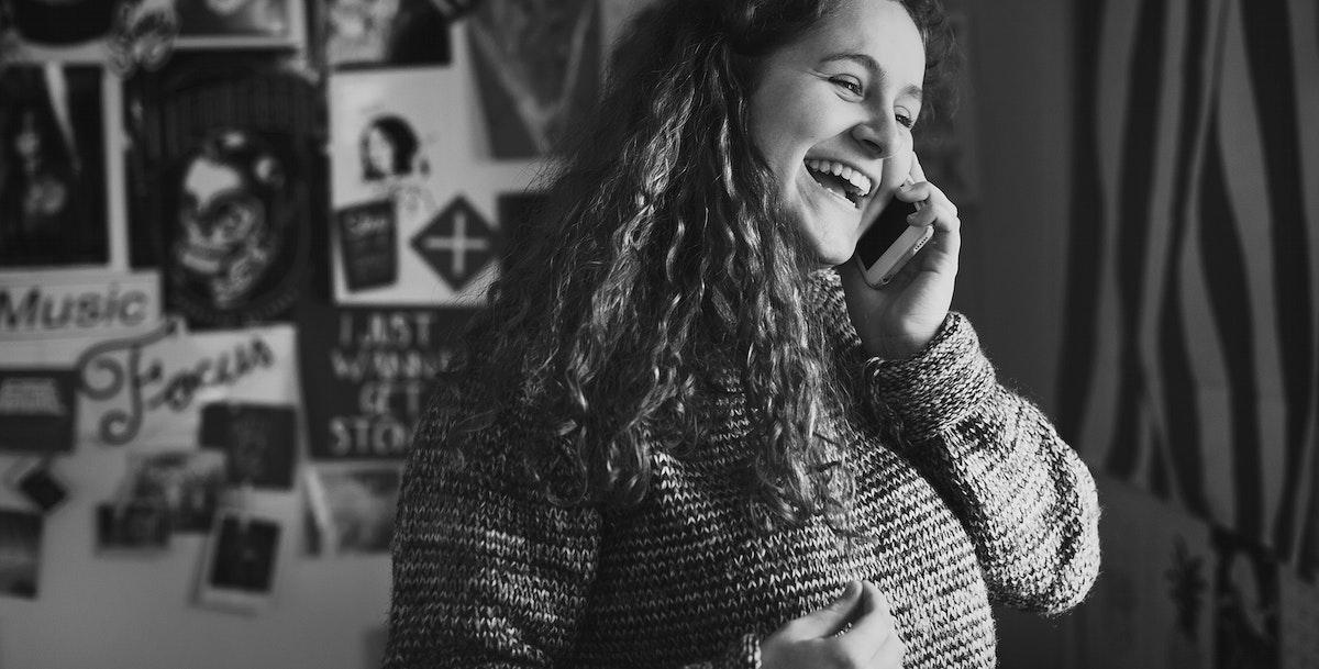 Teenage girl talking on a phone in a bedroom