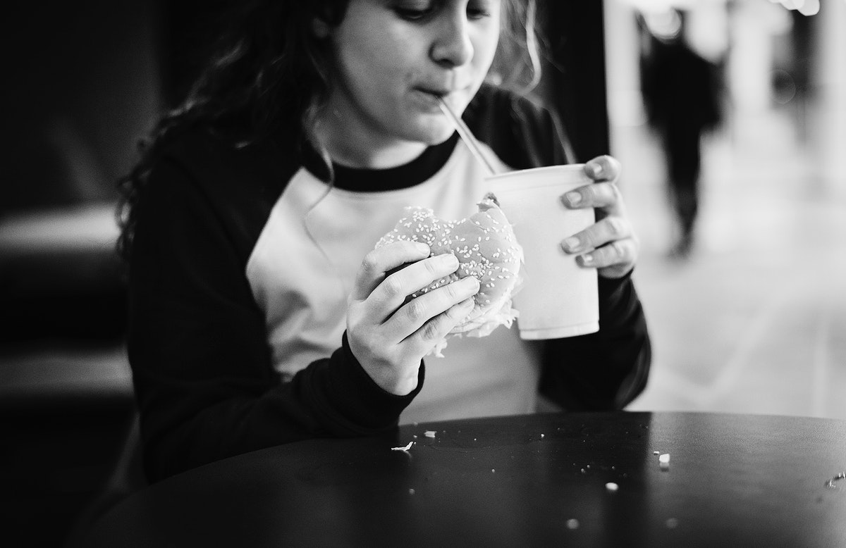 Close up of teenage girl eating hamburger