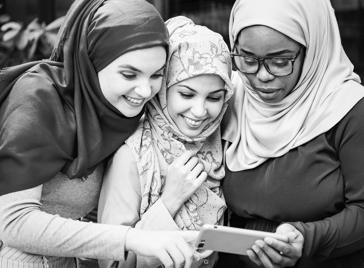 Muslim women looking into a mobile