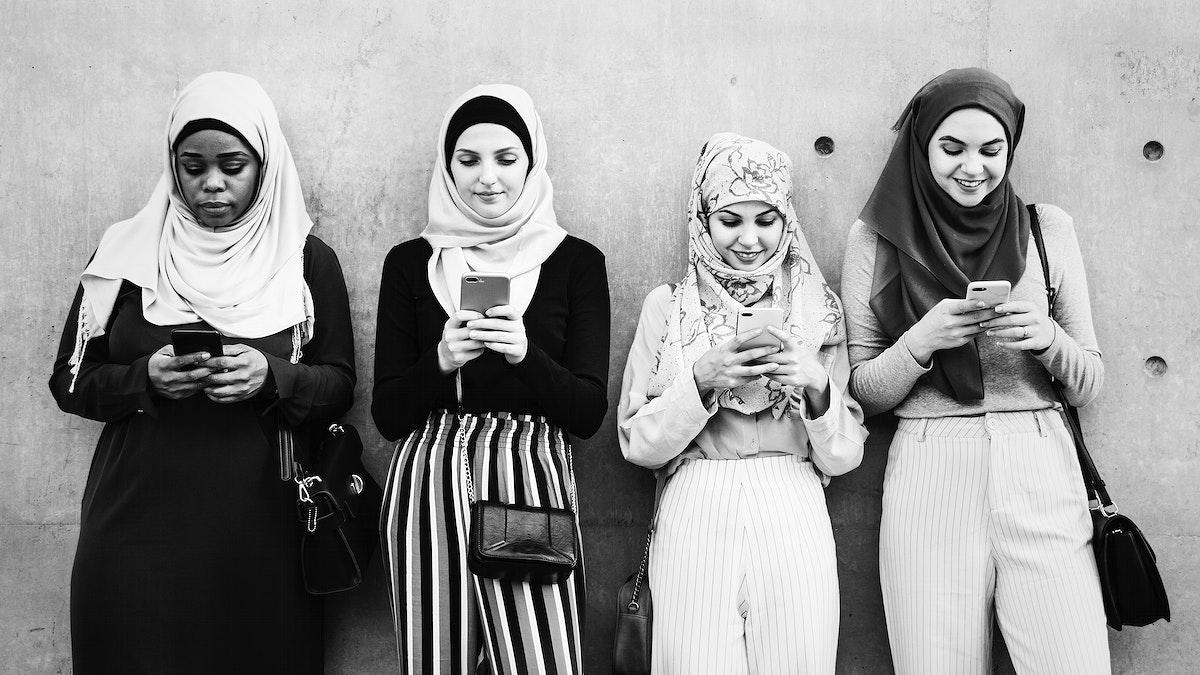 Muslim girls using smartphones in a row