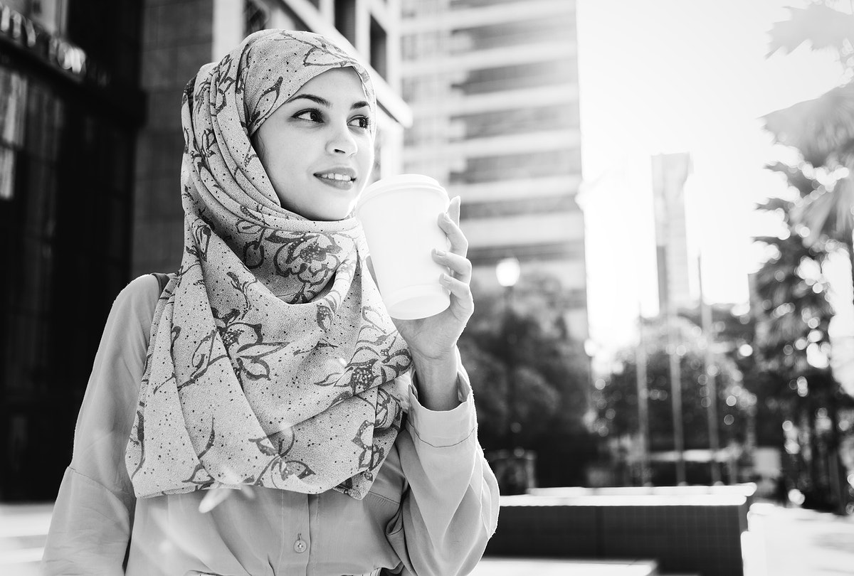 Muslim woman drinking coffee in the city