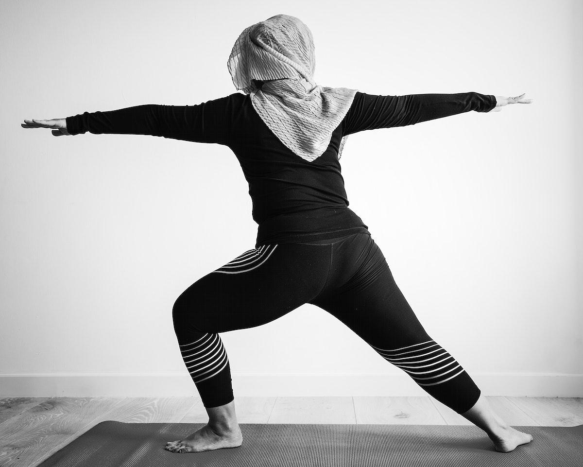 Muslim woman practicing yoga at home
