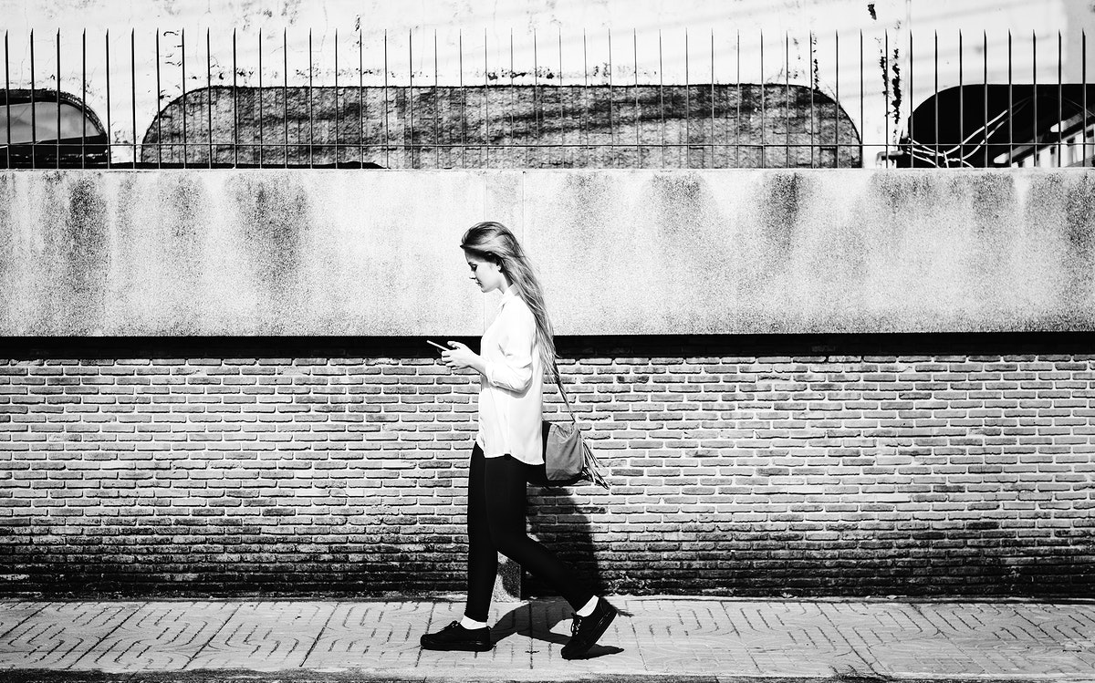 Young woman using smartphone and walking