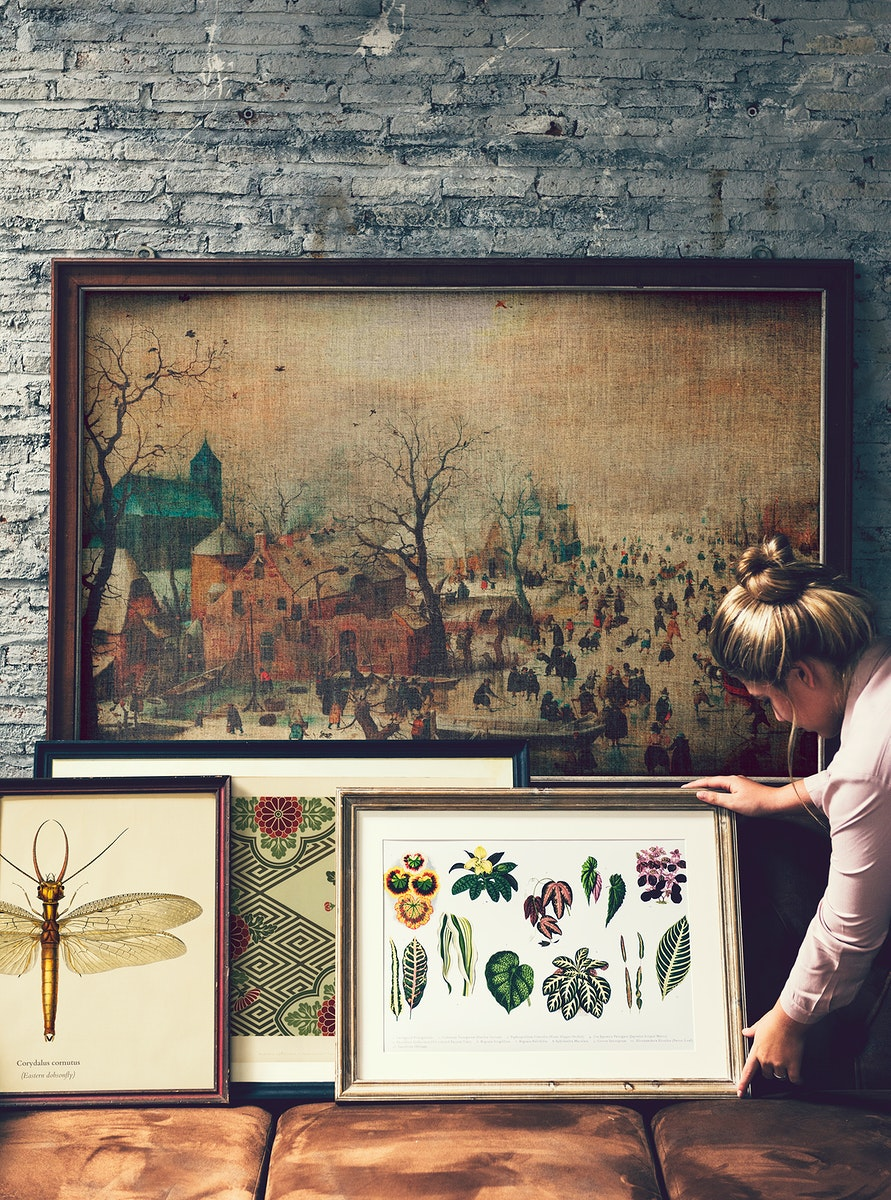 Woman arranging picture frames and art