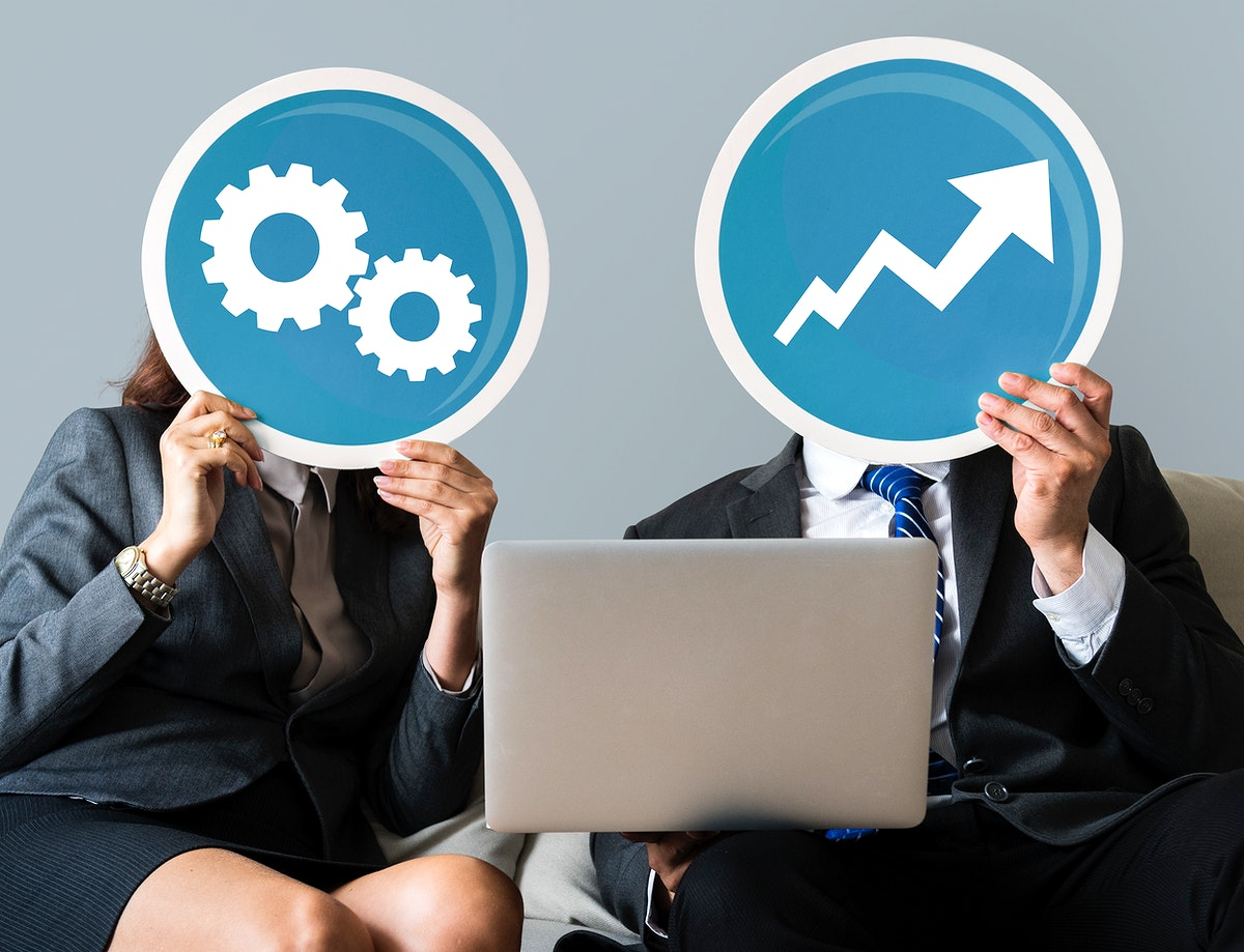 Business people holding gear and growth icons