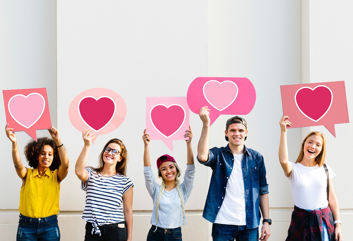 Young adult friends holding up heart icons