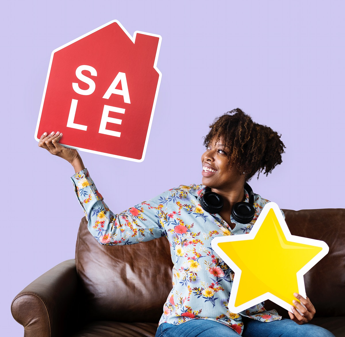 Cheerful woman holding a house sale and star icons