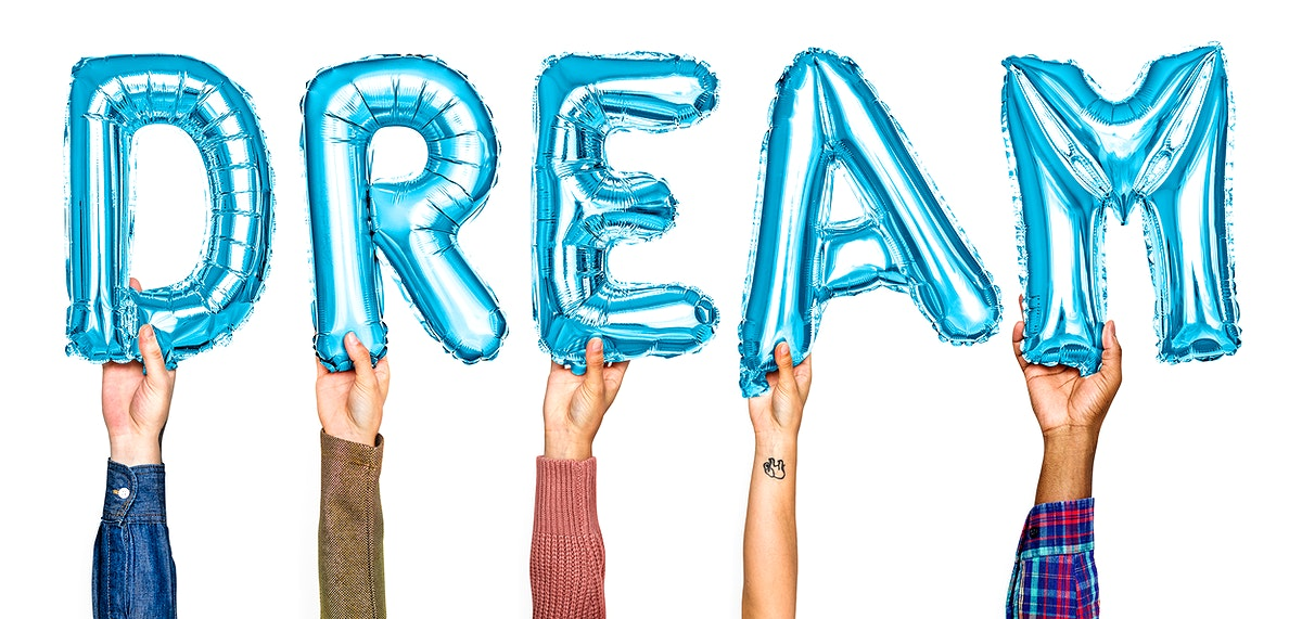 Hands holding balloons spelling Dream