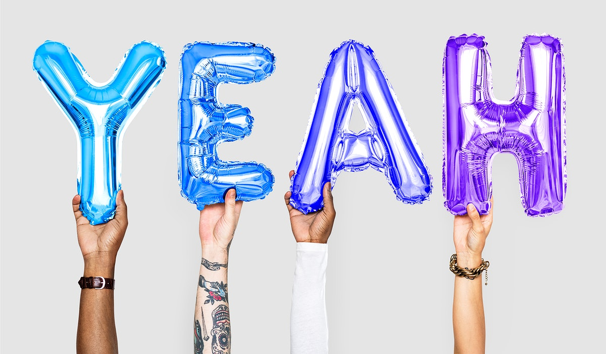Hands holding balloons spelling Yeah