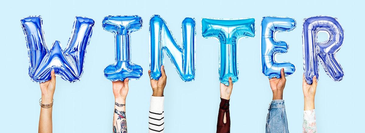 Hands holding balloons spelling Winter