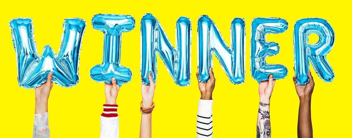 Hands holding balloons spelling Winner