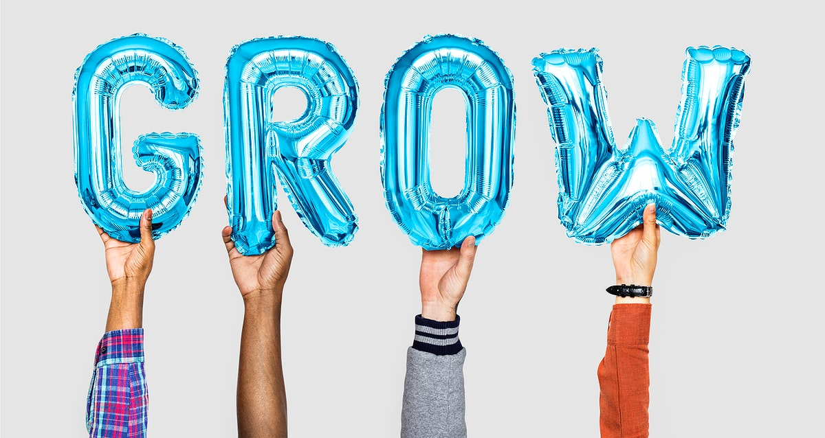 Hands holding balloons spelling Grow