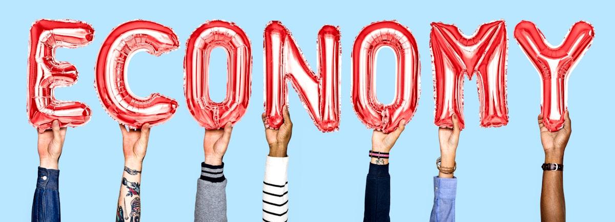 Hands holding balloons spelling Economy