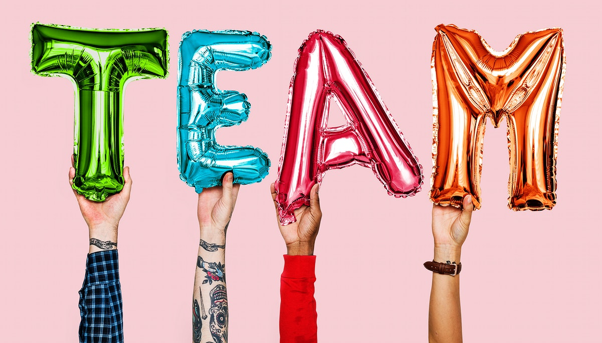 Hands showing team balloons word