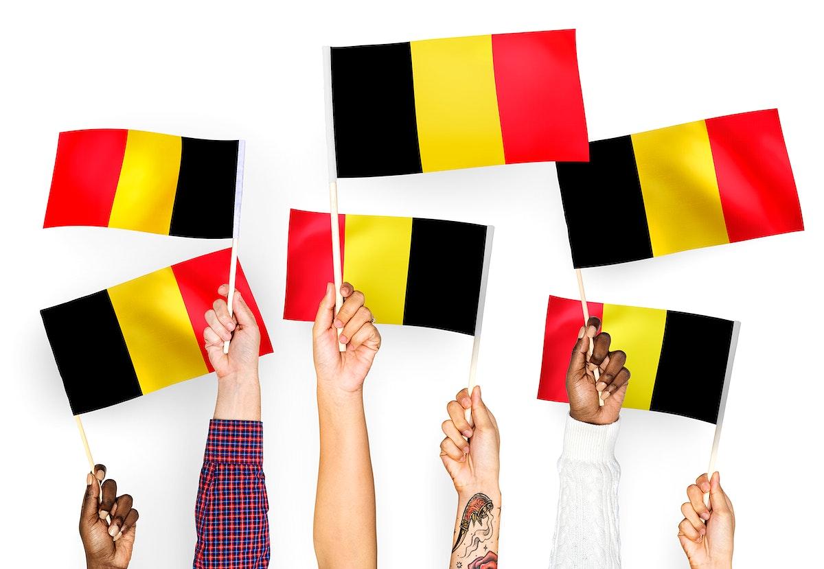 Hands waving the flags of Belgium