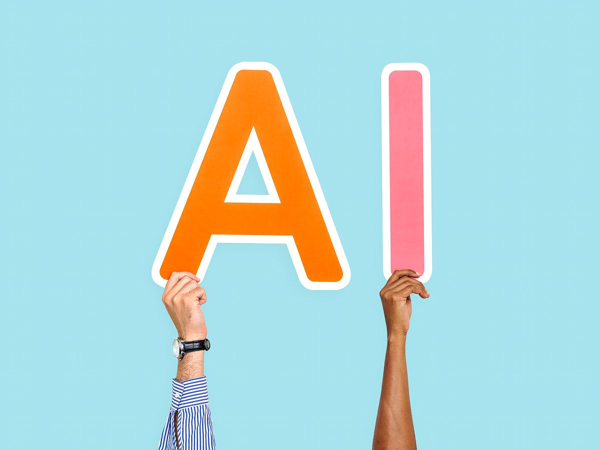 Hands holding up colorful letters forming the abbreviation AI