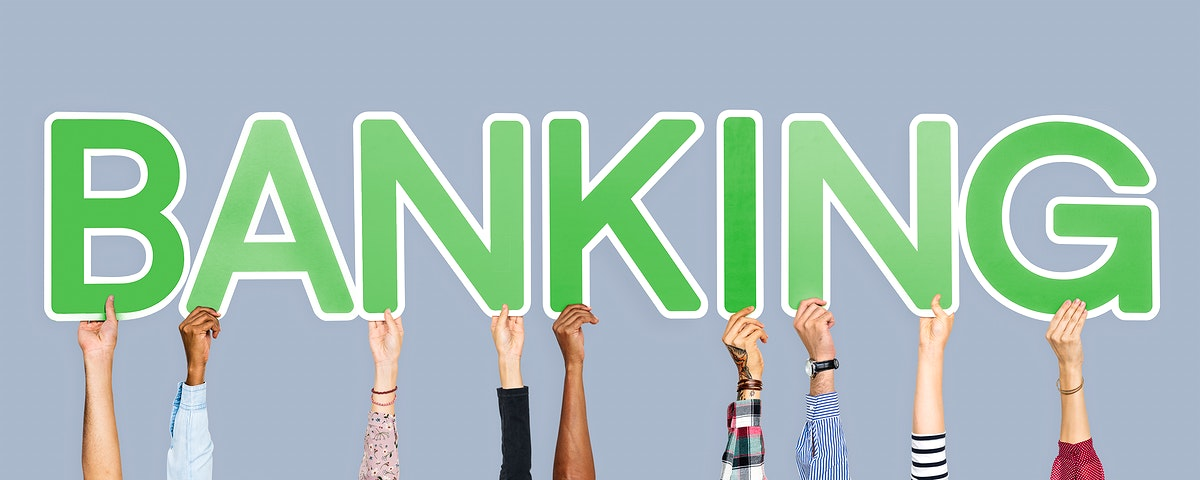 Hands holding up green letters forming the word banking