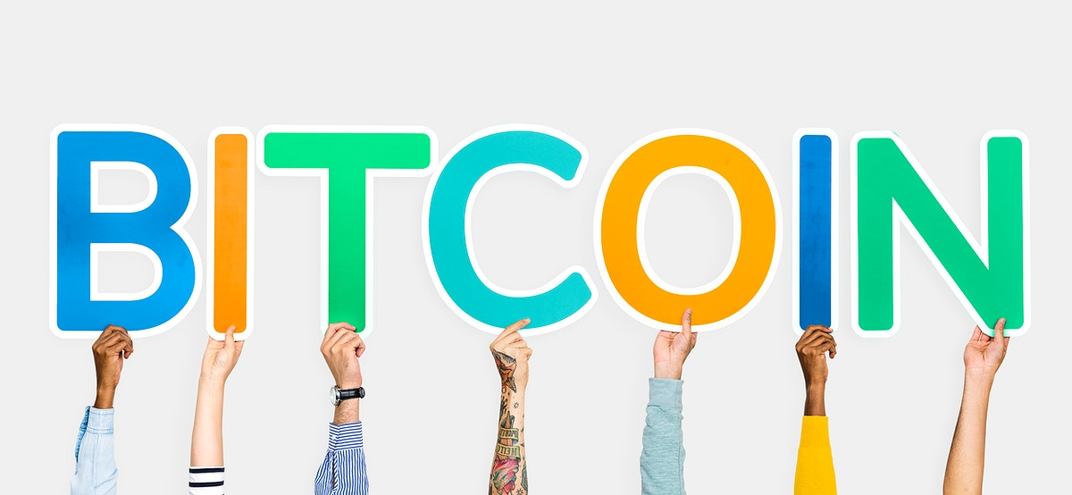 Hands holding up colorful letters forming the word bitcoin