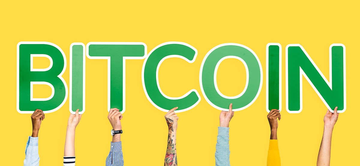 Hands holding up green letters forming the word bitcoin