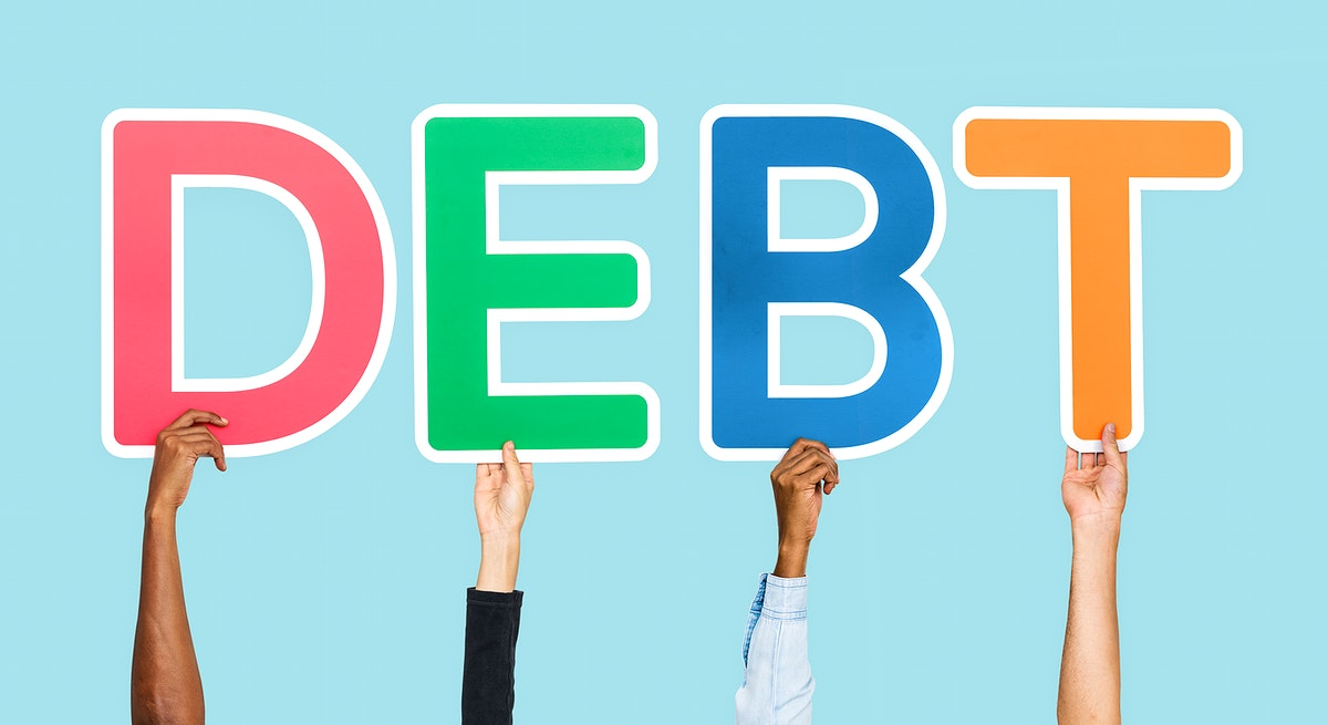 Hands holding up colorful letters forming the word debt