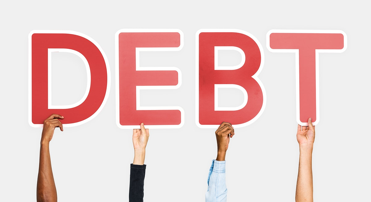 Hands holding up red letters forming the word debt