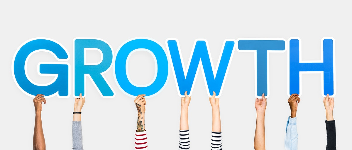 Hands holding up blue letters forming the word growth